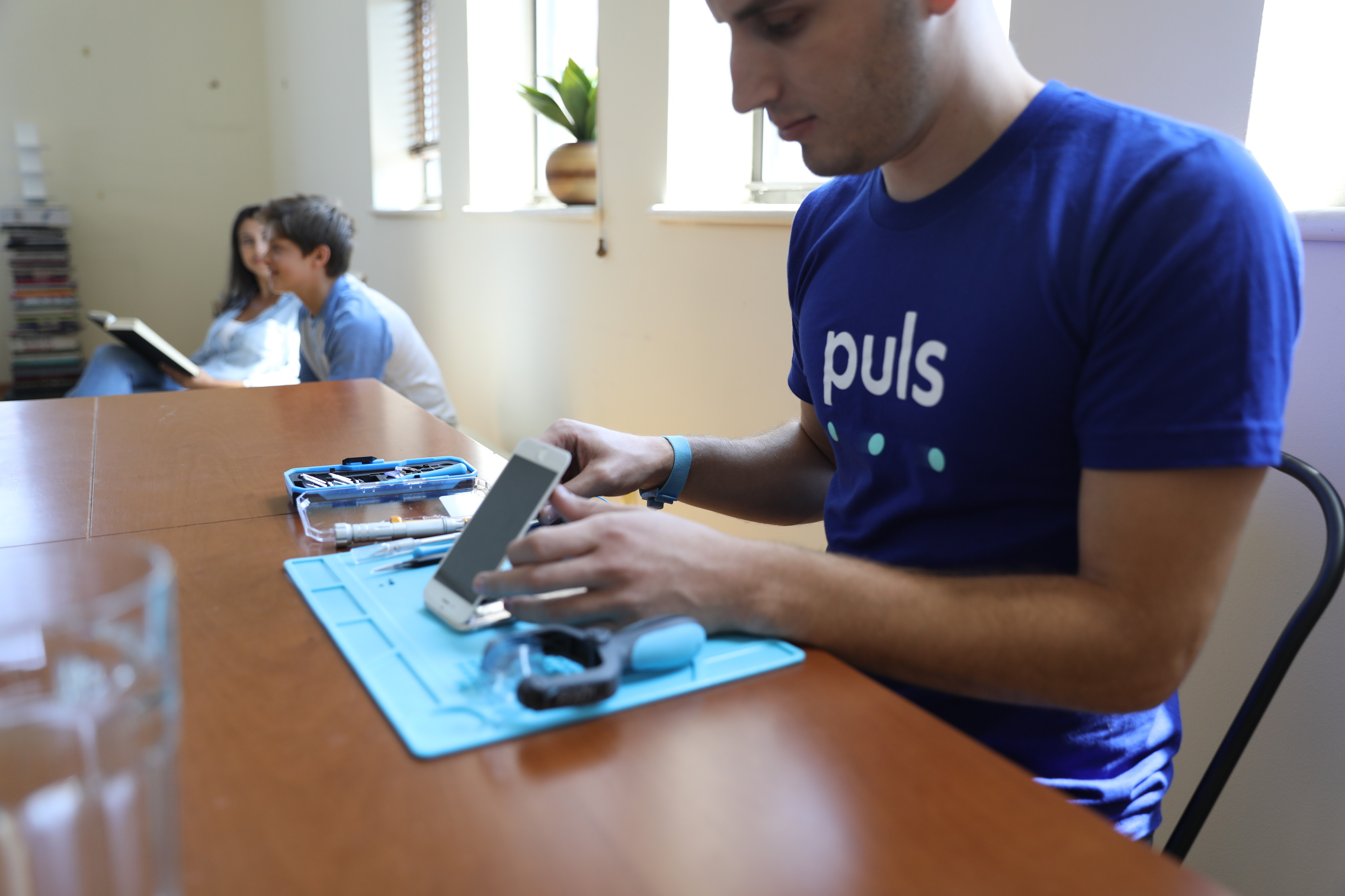 Puls technician fixing an iPhone