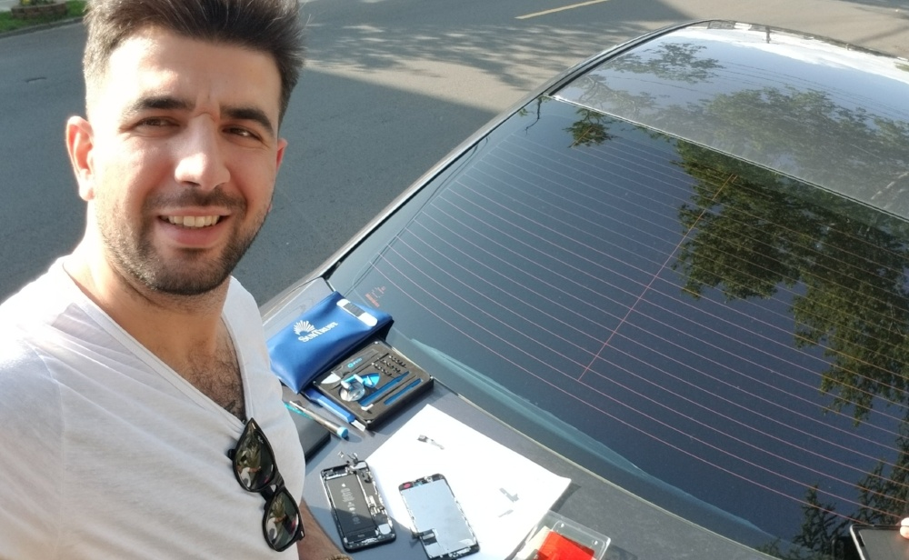 technician Ayhan Sagir repairing a phone on a car