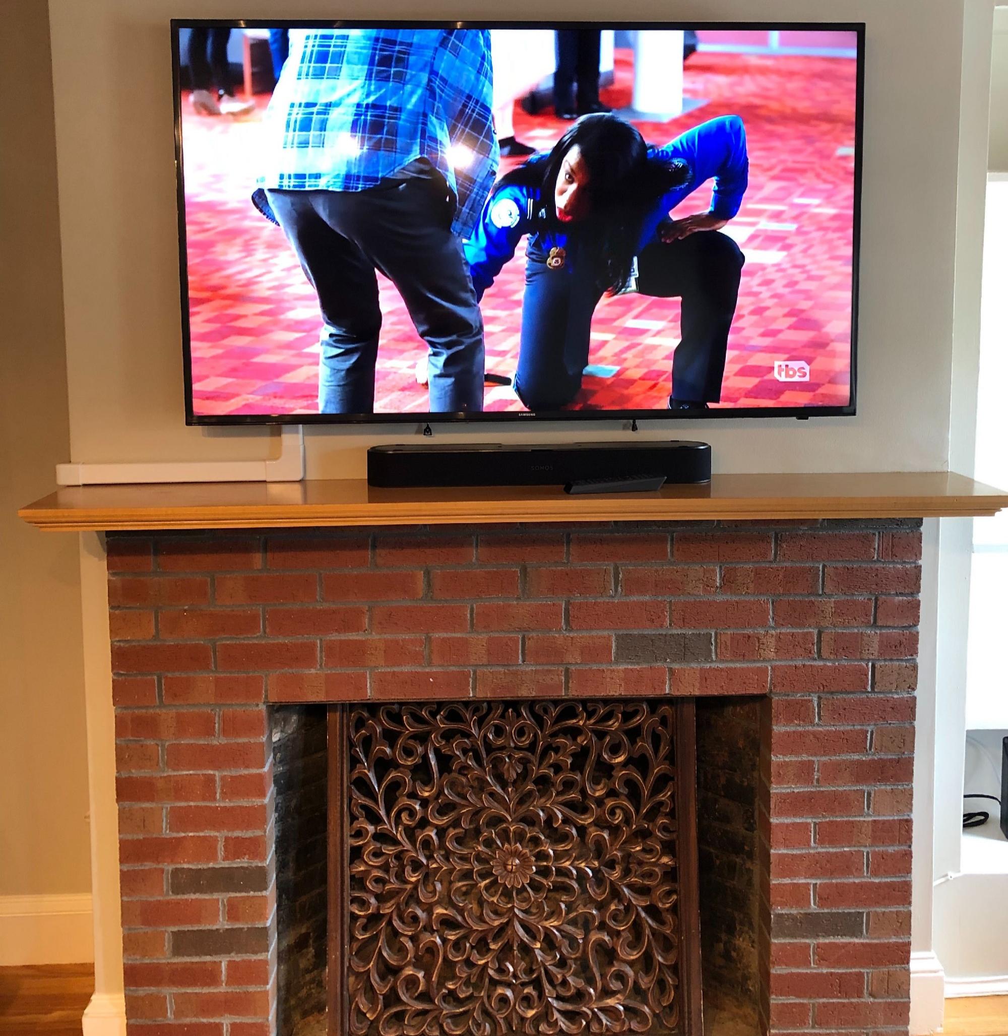 TV mounted above brick fireplace