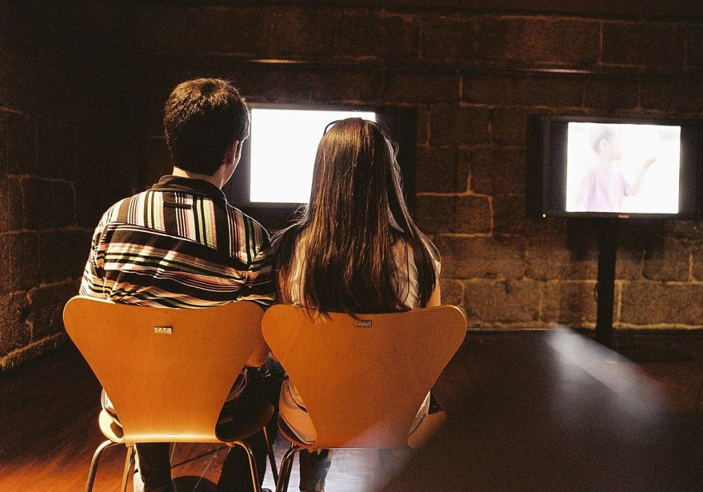 image of couple sitting in front of a tv