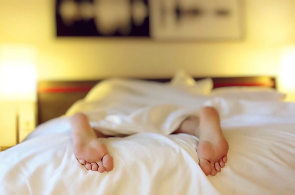 picture of persons feet hanging on end of bed with restless sleep