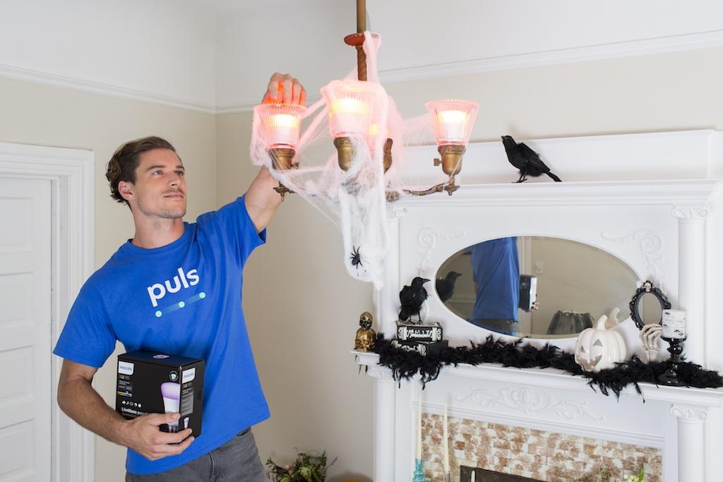 man installaing hue lights in living room