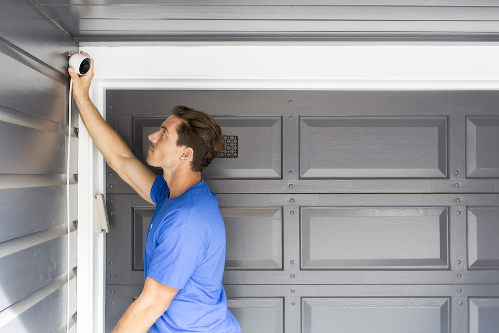 man installing nest security camera in gargage