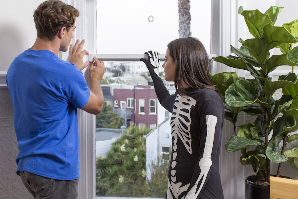 man and woman installing samsung smart things sensor on window