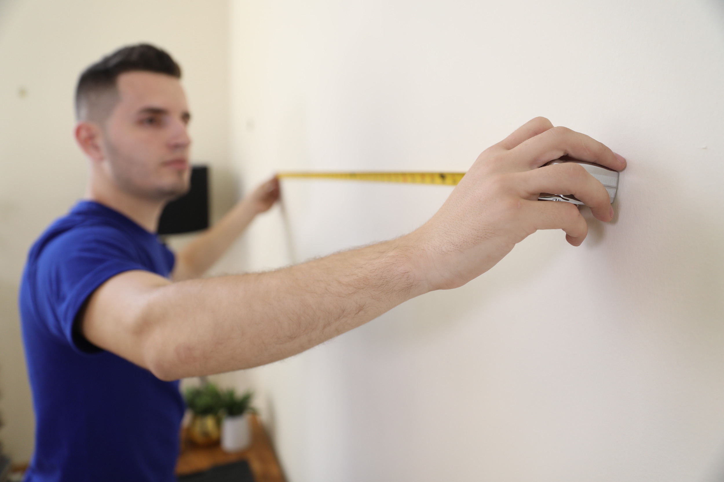 man measuring for tv wall mount