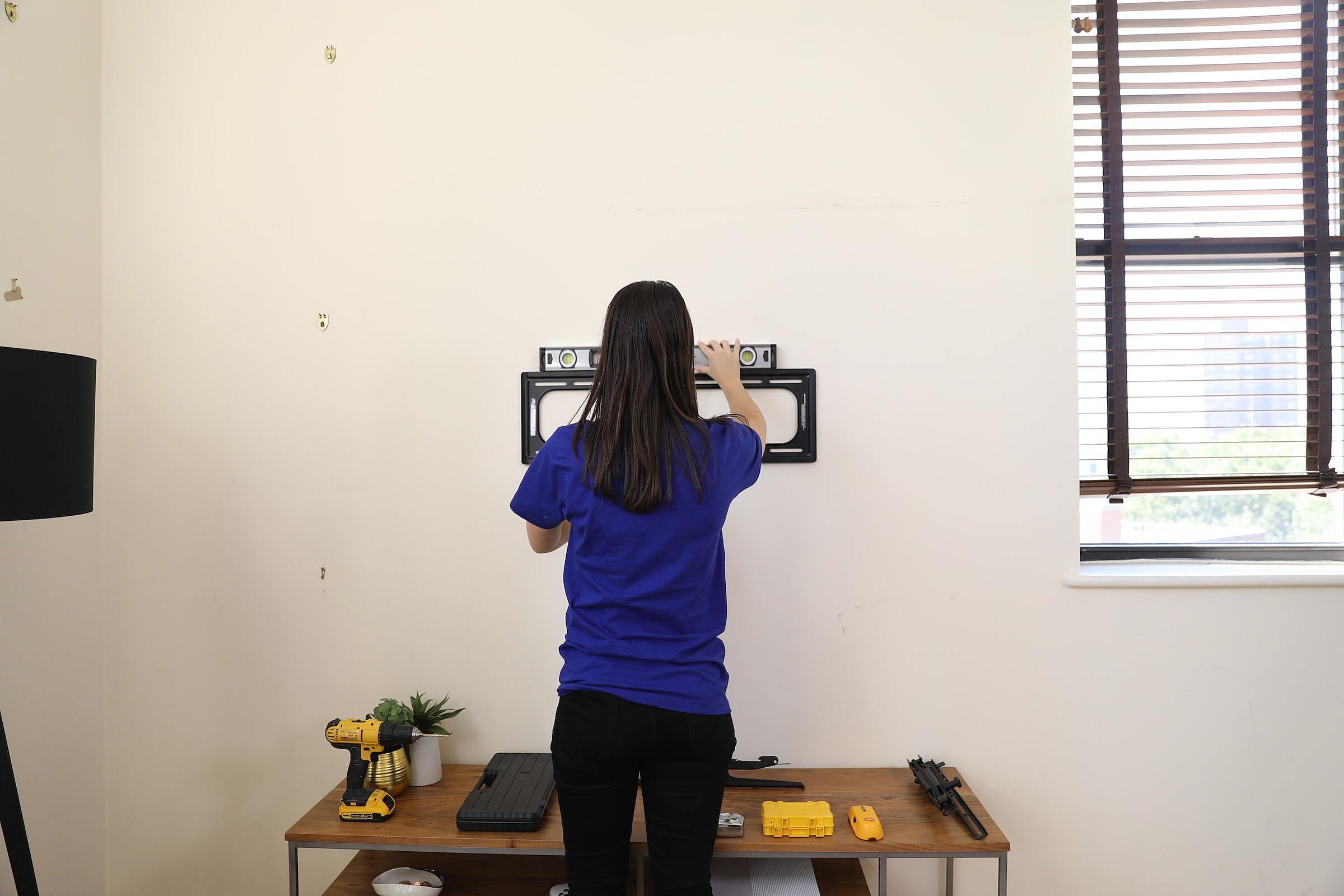 girl hanging tv mount on wall