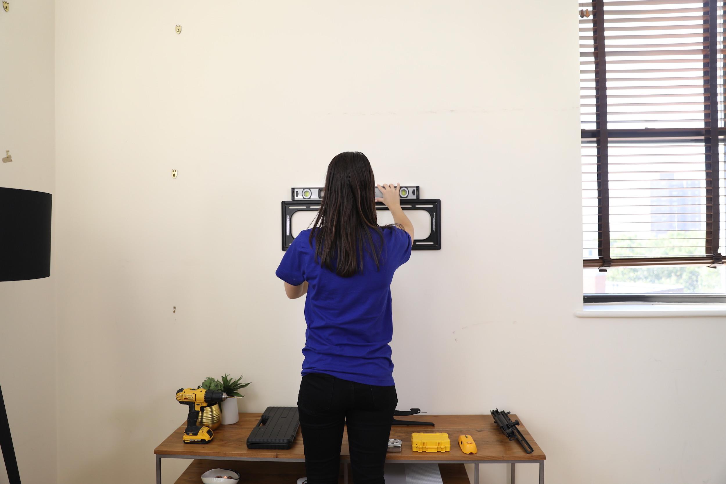 girl hanging tv mount on wall