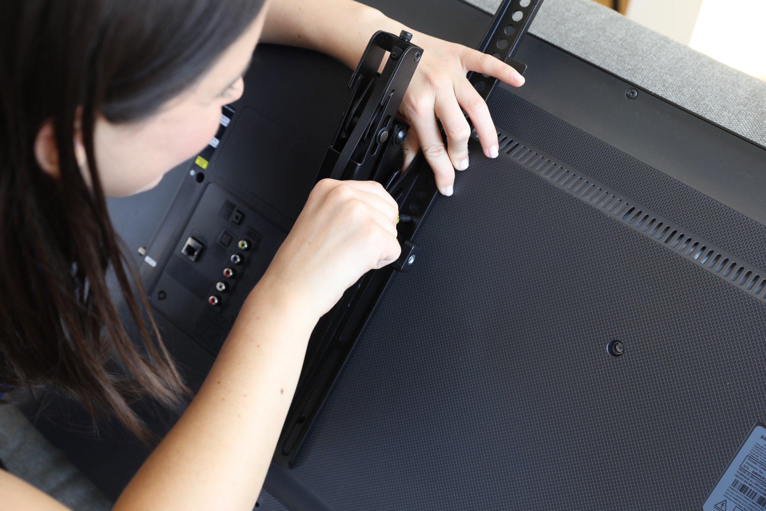 girl attaching mount to back of tv