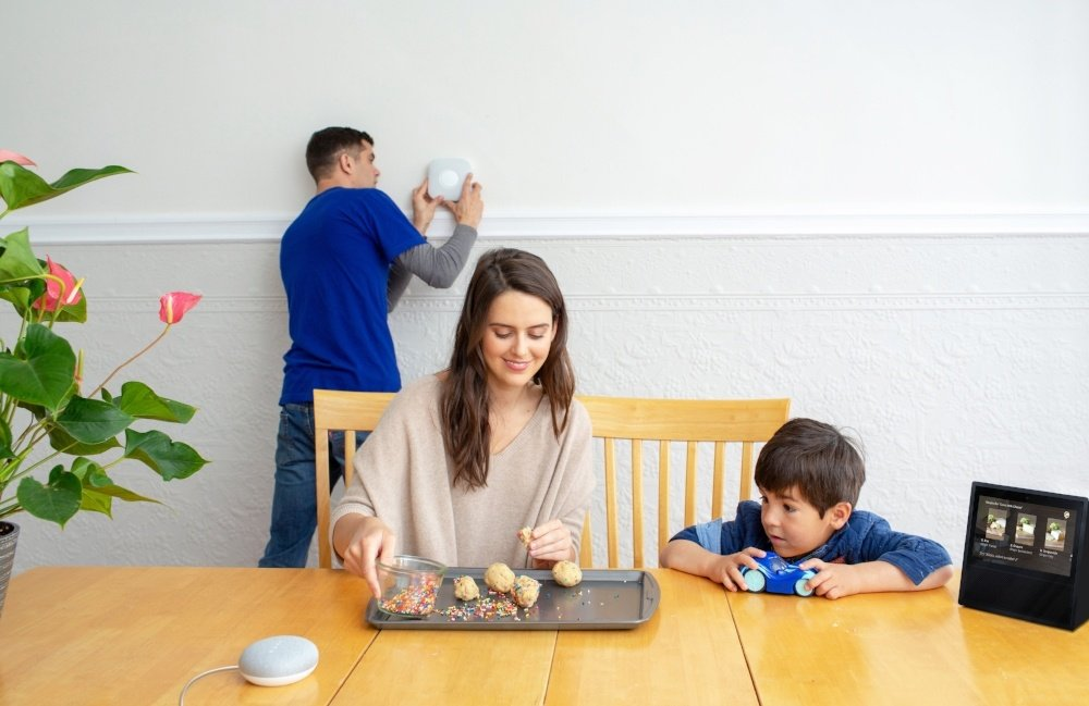 family baking cookies with smart devices