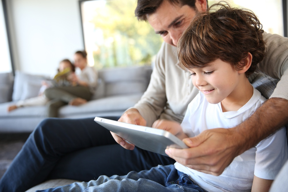 father and son playing with tablet