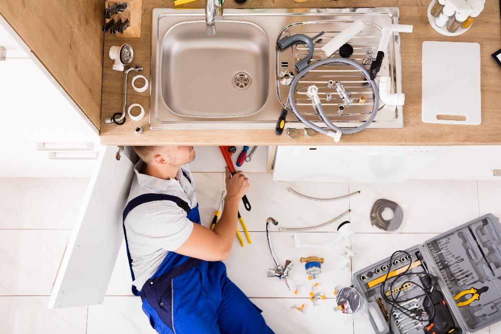 plumber fixing leaky sink